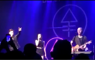 Christina Grimmie's band giving the 'devils horn' and its logo in the background, the alchemical symbol for phosphorous, which is commonly associated with Lucifer in occult circles.